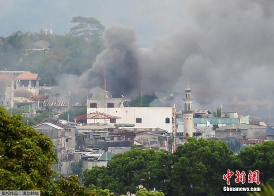 """当地时间5月25日,菲律宾棉兰老岛马拉维市,菲律宾军方使用直升机对剩余的约40名""""穆特组织""""等反政府武装成员发动打击。自5月23日发生交火以来,已有31名武装分子被打死,另有13名军警死亡、40名军警受伤。图为被直升机攻击后,建筑腾起浓烟。"""