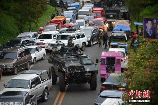 当地时间5月25日,菲律宾马拉维市,当地民众驾车逃离马拉维市,道路严重拥堵,菲军方装甲车穿行其间。