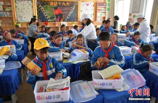 资料图:藏区孩子们正在查看自己收到的爱心包。 刘忠俊 摄