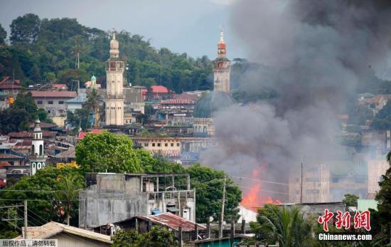 """当地时间5月27日,菲律宾马拉维,政府军出动多型号战机,持续向""""毛特""""反政府武装发起进攻。图为一处建筑起火。"""