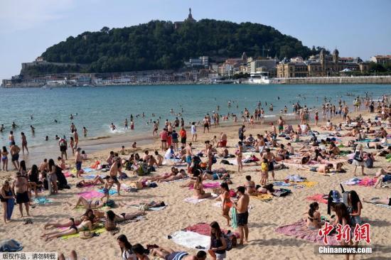 資料圖:西班牙海灘游人扎堆曬日光浴。