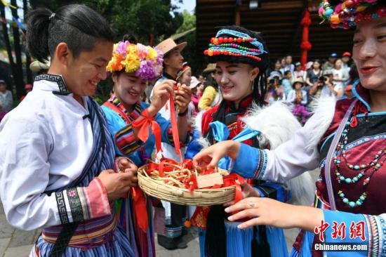 5月28日,云南普米族在昆明云南民族村内与其他少数民族和游客一起庆祝其传统情人节。中新社记者 任东 摄