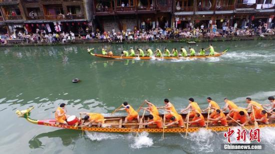 5月29日,湖南凤凰古城一年一度的端午龙舟赛在沱江河上开赛,居民和游客们纷纷在河岸与吊脚楼上围观这项已拥有百年历史的传统赛事。 杨华峰 摄