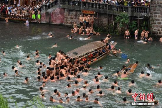 5月30日,正值端午佳节,湖南凤凰古城的沱江河上演抢鸭子大战,众多居民与游客纷纷跳入河中,争抢从吊脚楼上抛下的鸭子,以此方式庆祝端午节的到来。 杨华峰 摄