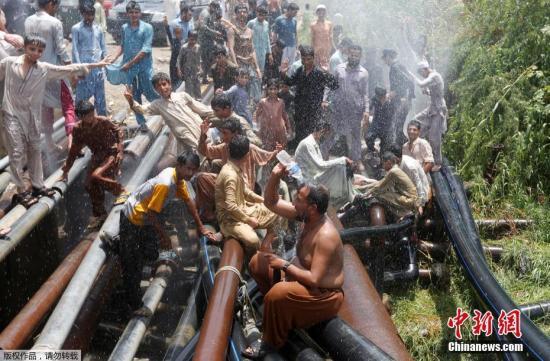 当地时间5月30日,在巴基斯坦城市卡拉奇,人们聚集在一起用水管喷水消暑降温。