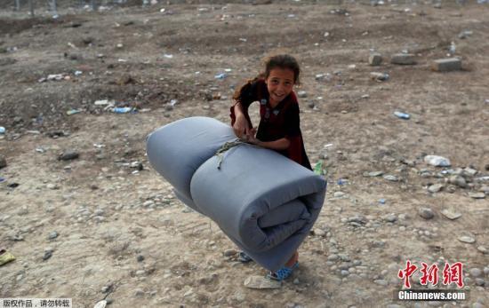 2017年4月27日,一名无家可归的伊拉克女孩拖着被褥,来到摩苏尔南部的一个难民营。