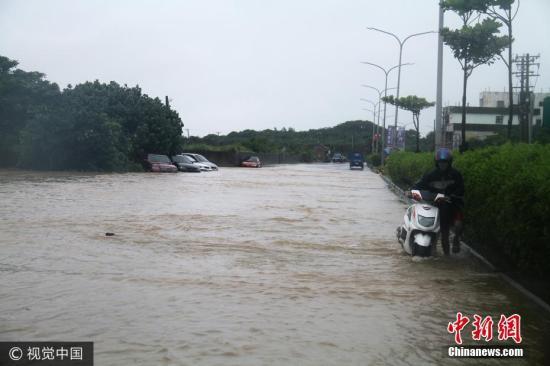 资料图:台湾暴雨来袭,骑摩托车者推车前行。图片来源:视觉中国
