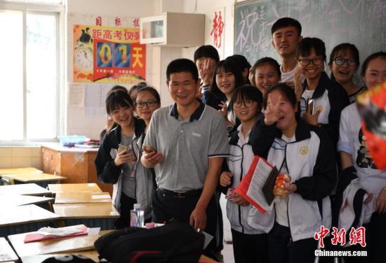 """6月4日,学生与老师合影留念,告别自己的高中生涯。每年的此刻,安徽省六安市毛坦厂""""高考镇""""都会重复上演这一时刻,5日,这些高考学子将乘坐大巴赶考,以冀实现他们的""""大学梦""""。中新社记者 韩苏原 摄"""