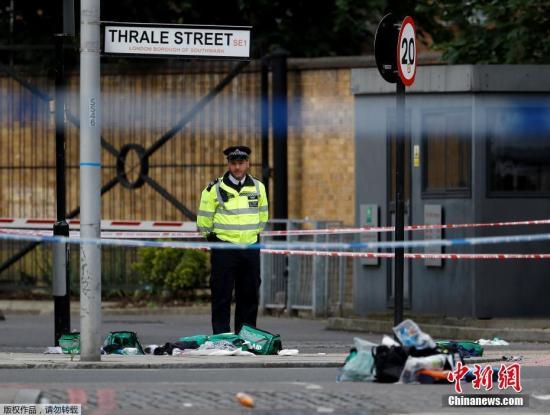 """在位于伦敦桥附近巴罗集市(Borough Market),两名男子持刀行凶。其中1名男性嫌犯被警察击中后倒地,身上还绑有小型金属容器。图为警察在巴罗集市对现场进行封锁。据CNN报道,极端组织""""伊斯兰国""""有关的媒体宣称,该组织成员为袭击负责。但是,有分析称,该组织并不能提供任何证据证明与此案有关。"""