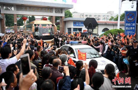 6月5日上午,安徽毛坦厂中学考生出发,万余民众冒雨相送。8时08分,28辆大巴车从毛坦厂校园缓缓开出,毛坦厂镇过万民众夹道欢送。 中新社记者 韩苏原 摄