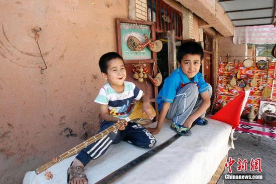 """喀什古城喀赞其亚贝西巷一家乐器店铺""""小老板"""",叫卖自家手工乐器。王小军 摄"""