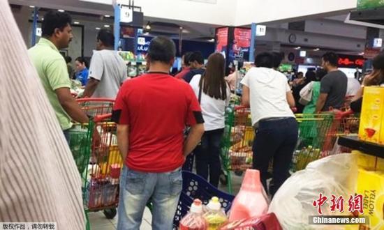 民众聚集超市抢购物资。