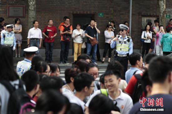 """6月7日,2017年高考大幕正式拉开,上海5万余名考生步入考场,参加考试。据悉,今年是上海第一年实施全新的高考改革方案,实施""""3+3""""新高考方案。图为上海交警保障考点周边安静有序。 记者 张亨伟 摄"""