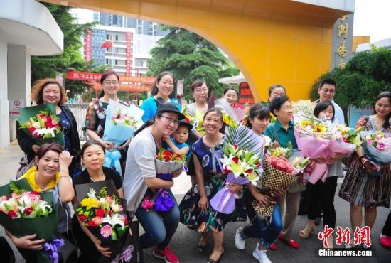 6月8日,山东济南众多妈妈手捧鲜花,等候即将结束高考的学子。中新社记者 张勇 摄