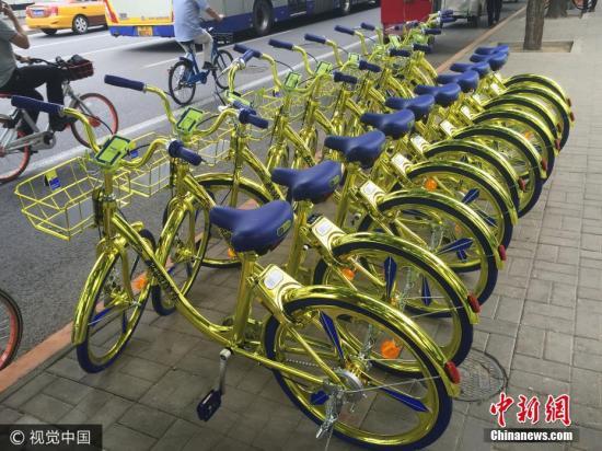资料图:6月8日,北京,金色共享单车现身朝阳区望京街头。该共享单车配备充电模块,可以给手机充电。 图片来源:视觉中国