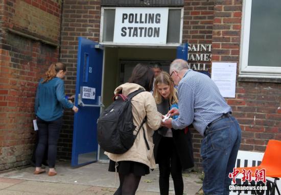 6月8日,英国举行大选,650个选区的选民前往投票站,选出代表各自选区的国会议员,赢得全国超过半数选区议席(即超过326个席位)的政党,则获得执政权。图为投票站工作人员在核对选民身份信息。<a target='_blank' href='http://www.chinanews.com/'>中新社</a>记者 周兆军 摄