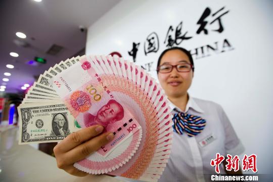山西太原,银行工作人员展示人民币、美元。 张云 摄