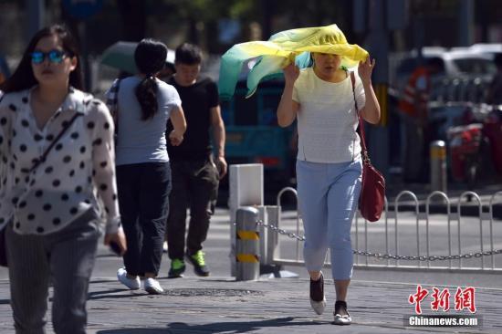 """6月9日,北京天气进入""""高烤""""模式,最高气温将达37度。据北京市气象台预报,今天最高温将达37℃,午后地表温度或可超过60℃。当日,北京仍处在高温蓝色预警中,""""高烤""""模式继续,紫外线很强,出行需注意防暑防晒勤补水,体弱人群中午前后尽量避免户外活动。图为北京三里屯SOHO附近行人避暑防晒""""各显神通""""。记者 金硕 摄"""