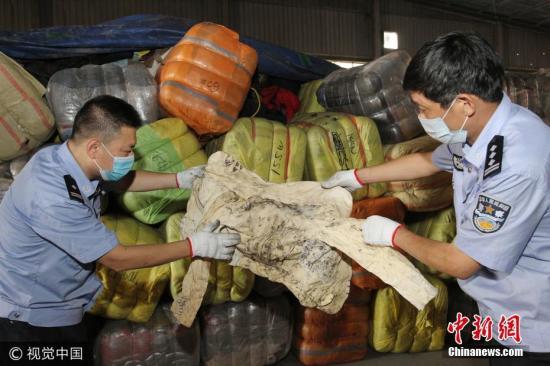 """厦门海关查获一起海上偷运走私""""洋垃圾""""案件,查获来自韩国的旧服装3596包、共计500吨。许多衣服上带有明显的穿着痕迹和污渍,部分内衣上甚至还带有血渍,办案人员在清点过程中,还发现了大量童装。文字来源:法制网 图片来源:视觉中国"""
