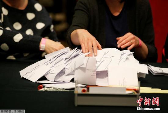 英国大选实行简单多数选举制度,在全国650个选区中,选民投票选出各自所在选区的政党代表,得票最高者获胜,成为下议院议员。赢得全国超过半数选区议席(即超过326个席位)的政党获得执政权,该党领袖将成为英国首相。图为肯德尔投票站内,工作人员正在忙碌。