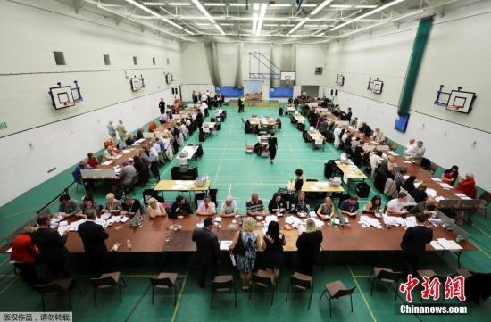 保守党领袖特雷莎・梅当天携丈夫菲利普回到她所属的选区伯克郡投票,工党领袖科尔宾在伦敦北部的伊斯灵顿投票。其他几大政党领导人也都回到各自所在选区投票。图为黑斯廷斯投票站,工作人员在清点票数。