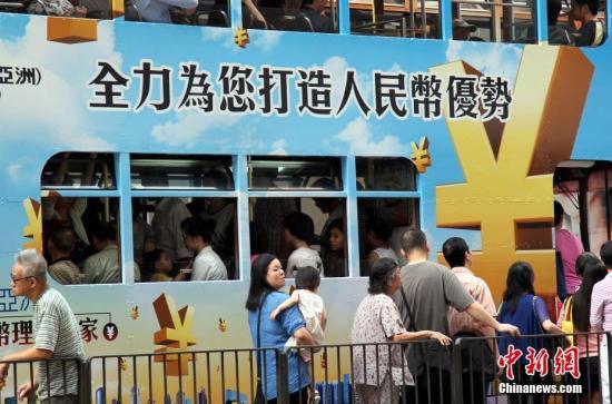 """资料图:香港""""叮当车""""上的人民币广告。中新社记者 洪少葵 摄"""