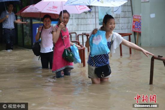 图为南京市雨花台区,市民在水中艰难出行。图片来源:视觉中国
