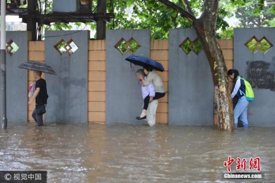 6月10日,南京市雨花台区,市民在水中艰难出行。图片来源:视觉中国