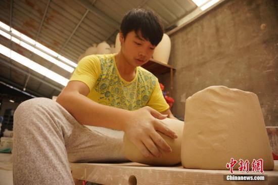 一位稚气未脱的小学徒在反复揉捏、摔打一块瓷泥,以求制作出来的瓷胎坚实。