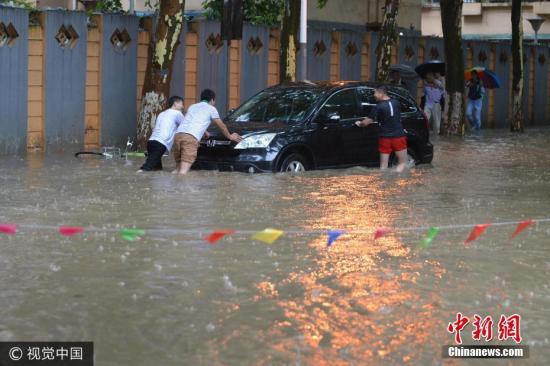 图为6月10日,南京市雨花台区,几个男子推着抛锚的汽车。来源:视觉中国