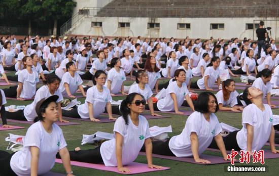 资料图:瑜伽爱好者躺在瑜伽垫上进行瑜伽表演。 邹海斌 摄