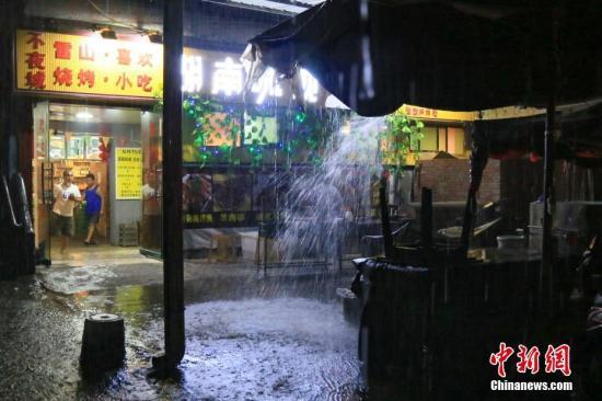 6月10日晚,贵州省雷山县遭受暴雨袭击。图为雷山民众在夜市中避雨。 中新社记者 贺俊怡 摄