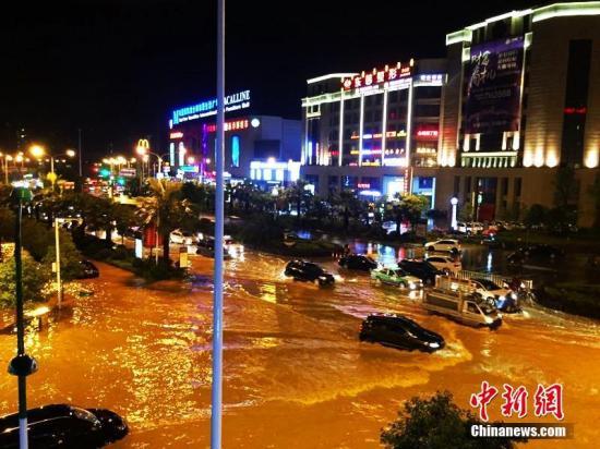 """6月11日晚,福建宁德市迎来短时雷阵雨,致使市区路段出现积水严重,有车辆被""""泡""""在水中。陈香秀 摄"""