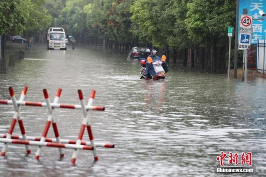 资料图:6月12日,贵阳市民骑电动车在积水路段行驶。<a target='_blank' href='http://www.chinanews.com/'>中新社</a>记者 贺俊怡 摄