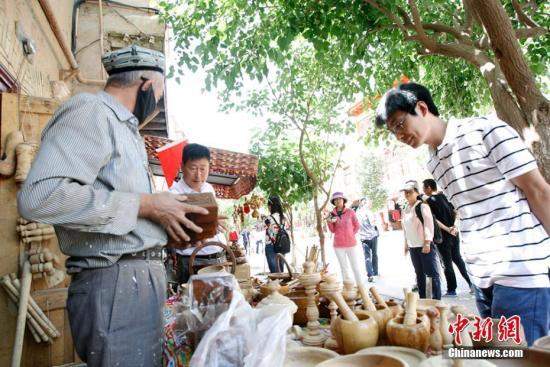 资料图:游客选购喀什手工艺品。王小军 摄