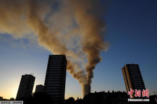 当地时间6月14日凌晨,伦敦西部一栋20余层的公寓大楼发生大火,火势猛烈,几乎蔓延到了所有楼层。约200名消防员和40辆消防车前往灭火。图为现场浓烟冲天。