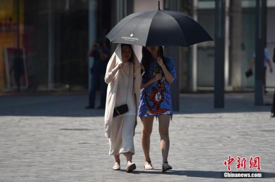 资料图:北京街头新人用衣服和伞遮阳。 中新网记者 金硕 摄