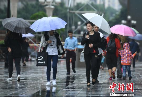 资料图:民众雨中出行。陈超 摄