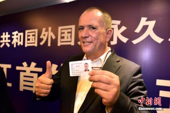 资料图:来自德国的谢非(中文名)领到《中华人民共和国外国人永久居留身份证》。 中新社发 周尔博 摄