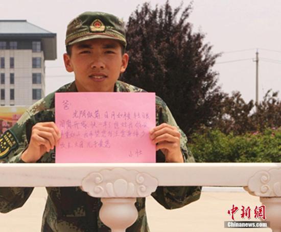 资料图为官兵手写一句句质朴的语言,向远方的父亲送去深情祝福。成伟 摄
