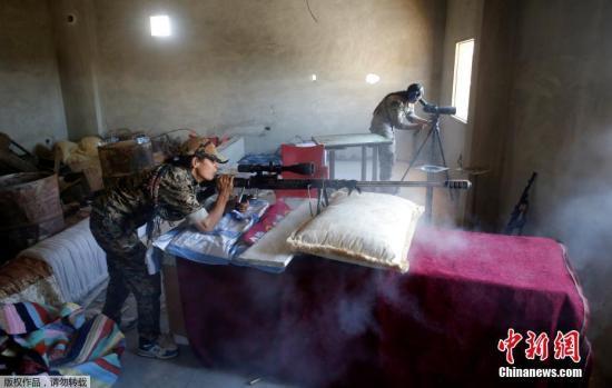 当地时间2017年6月18日,叙利亚拉卡,库尔德武装继续在拉卡推进,围剿极端组织。图为两名库尔德武装的女兵在掩体中配合,对极端分子进行狙击。