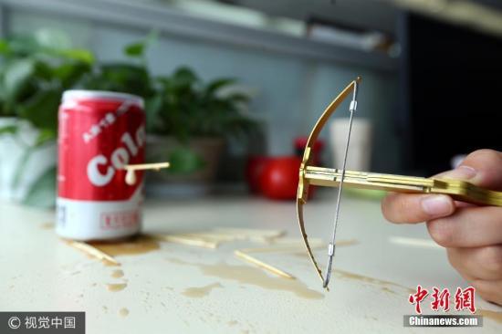 """资料图:图为""""牙签弩""""射击易拉罐。 王红强 摄 图片来源:视觉中国"""