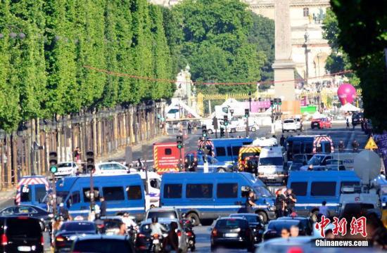 """6月19日下午,一男子驾车在巴黎香榭丽舍大道上突然冲撞宪兵部队的巡逻执勤车辆。肇事车辆随即起火,驾车者身受重伤,最终不治身亡。警方无人伤亡。目前,法国内政部已将该事件定性为""""恐怖袭击图谋"""",巴黎检方反恐部门随即展开调查。据报道,肇事者是一名威胁国家安全的S级人物,其车辆上也发现了手枪、自动步枪和燃气罐。图为警方封锁香榭丽舍大道事发路段。 中新社记者 龙剑武 摄"""