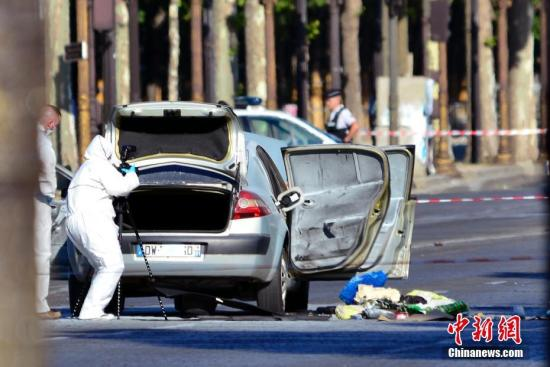 """6月19日下午,一男子驾车在巴黎香榭丽舍大道上突然冲撞宪兵部队的巡逻执勤车辆。肇事车辆随即起火,驾车者身受重伤,最终不治身亡。警方无人伤亡。目前,法国内政部已将该事件定性为""""恐怖袭击图谋"""",巴黎检方反恐部门随即展开调查。据报道,肇事者是一名威胁国家安全的S级人物,其车辆上也发现了手枪、自动步枪和燃气罐。图为鉴证人员在勘察现场。 中新社记者 龙剑武 摄"""