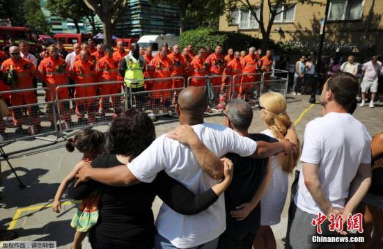 """6月20日消息,英国警方称,在日前发生的伦敦""""格伦菲尔塔""""公寓楼大火中,已经有79人""""推定死亡""""。这一数据还有可能发生变化。6月19日,英国民众举行活动,为此次事件中的遇难者默哀一分钟。图为肯辛顿附近民众和消防员共同为遇难者默哀。"""