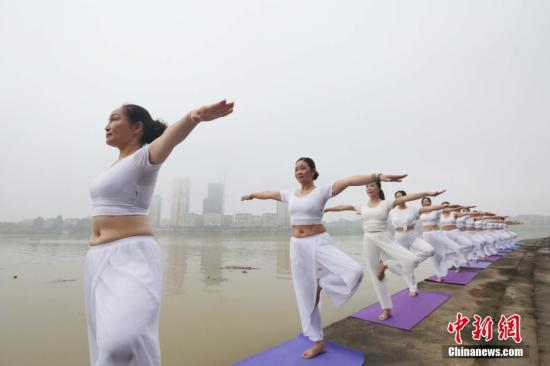 """6月21日""""国际瑜伽日"""",瑜伽爱好者在珠江上游的融江广西柳州市融安县城段江边晨练瑜伽。谭凯兴 摄"""