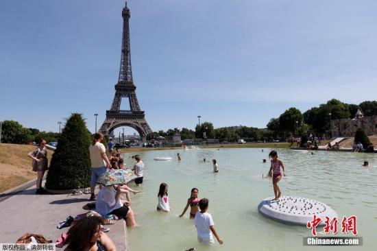 资料图:法国巴黎,民众在一处距埃菲尔铁塔不远的水池嬉水。