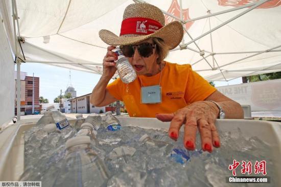 图为当地时间6月19日,美国亚利桑那州凤凰城,一名志愿者用冰水降温,他们也用此方法帮助过往行人暂时躲避酷暑。近日,凤凰城的温度已经升至115华氏度,直逼历史最高值。