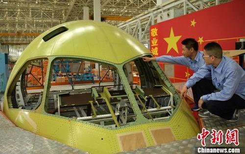 """改革开放以来中国制造业发展迅速,但多年来仍受困于""""大而不强"""",尤其体现在核心技术受制于人,品牌、产品质量不高,科技成果转化渠道不畅等。为解决这些问题,中国官方于2015年推出""""中国制造2025"""",全面部署提升制造业发展质量和水平,力争实现制造强国的战略目标。如今,该战略提出仅两年多,""""中国制造""""已在全球遍地开花,逐渐实现由""""低端""""向""""高大上""""的华丽转身。图为2017年5月4日成飞工程技术人员正对第三架C919大型客机""""机头""""进行出厂前的最后检验。中新社记者 刘忠俊 摄"""