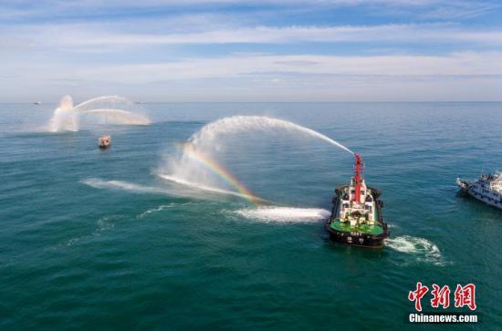 """6月22日,海南洋浦海上搜救分中心在洋浦经济开发区附近海域组织开展海上消防、救生以及商渔船碰撞应急处置演习。演习模拟一艘渔船与货轮发生碰撞,导致渔船船尾破损,渔船机舱着火,货轮救起两名落水渔民,一名渔民落水失踪,落水穿橙色救生衣。演习由""""海巡11502""""轮作为现场指挥船,""""浦消1号""""轮和""""洋港拖5""""轮负责扑灭渔船大火,""""洋浦渔政46071""""轮和""""洋海交2""""轮对事故渔船附近水域进行搜寻、警戒。图为航拍演习中""""浦消1号""""轮和""""洋港拖5""""轮扑灭渔船大火。 骆云飞 摄"""